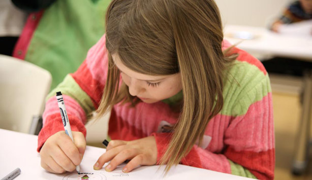 A girl draws during a homeschool workshop