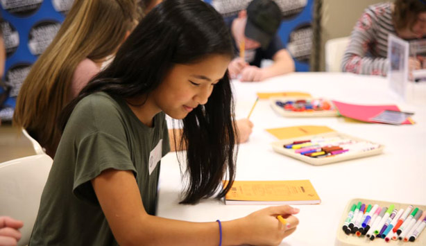 A girl writes during a homeschool teen workshop