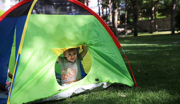 A child looks out from a tent during Sensory-Friendly