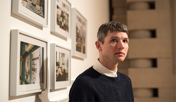 Luke Fowler stands in front of pictures of film stills