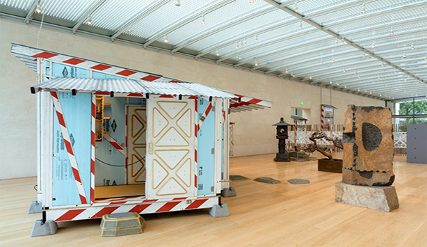 An image of the exhibition with the focus on a baby blue trailer with a slanted roof